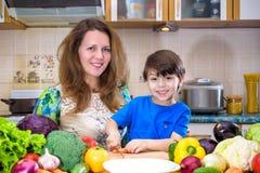 La jeune mère de cuisinier se tenant avec son petit fils dans le kitche Photo libre de droits