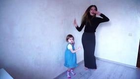 La jeune mère de soin joue avec la fille de bébé et enseigne à danser dans la chambre lumineuse pendant la journée banque de vidéos