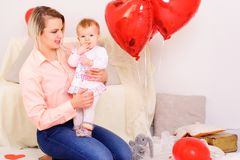 La jeune mère de sourire s'asseyent avec la petite fille sur des mains dans la chambre, Photo libre de droits