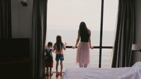 La jeune mère de vue arrière et deux les enfants heureux se tiennent ensemble à la grande fenêtre de chambre d'hôtel regardant fi clips vidéos