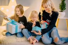 La jeune mère donne des cadeaux à ses petites filles image libre de droits