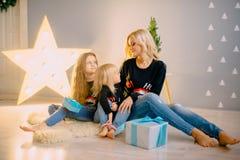 La jeune mère donne des cadeaux à ses petites filles images libres de droits