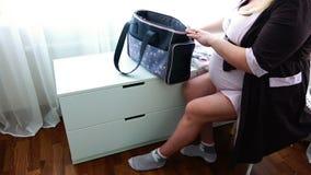 La jeune mère enceinte rassemble des choses dans la maison de maternité étant prête pour l'accouchement