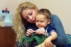 La jeune mère enseignent son petit tricotage de bébé Images libres de droits
