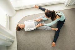 La jeune mère et la fille faisant le yoga de matin s'exercent photo libre de droits