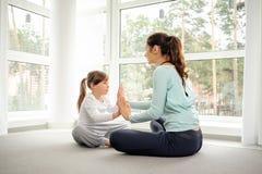 La jeune mère et la fille faisant le yoga de matin s'exercent photos stock
