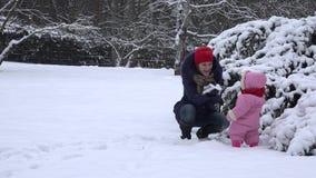 La jeune mère et le petit bébé ont l'amusement avec la neige 4K clips vidéos