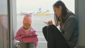 La jeune mère et la petite fille utilise les dispositifs à l'aéroport Photos stock