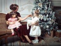 La jeune mère et ses deux petites filles s'approchent de l'arbre de Noël Photographie stock