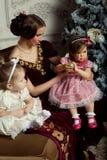 La jeune mère et ses deux petites filles s'approchent de l'arbre de Noël Image stock