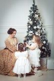 La jeune mère et ses deux petites filles s'approchent de l'arbre de Noël Photo libre de droits