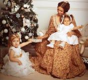La jeune mère et ses deux petites filles s'approchent de l'arbre de Noël dedans Photos stock