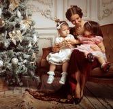 La jeune mère et ses deux petites filles s'approchent de l'arbre de Noël dedans Images libres de droits