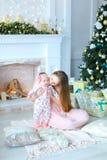 La jeune mère européenne tenant la fille dans des bras près a décoré la cheminée et l'arbre de Noël, portant la robe rose photos stock