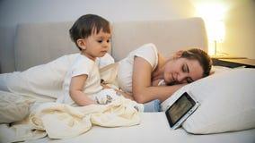 La jeune mère fatiguée est tombée endormi tandis que ses bandes dessinées de observation de fils d'enfant en bas âge sur le compr Photographie stock