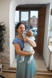 La jeune mère habillée dans le T-shirt et la jupe bleu-clair tient son fils minuscule sur ses bras dans la chambre à la maison photographie stock