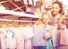 La jeune mère heureuse avec les enfants de achat de fille vêtx Photographie stock libre de droits