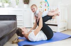 La jeune mère heureuse faisant la forme physique s'exerce avec ses 9 mois de bébé garçon Image libre de droits