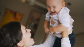 La jeune mère heureuse tenant son enfant nouveau-né et jette  Famille à la maison Belle maman de sourire et bébé heureux banque de vidéos