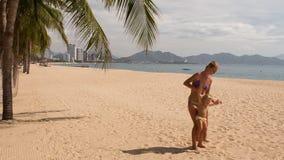 la jeune mère jette en l'air vers le haut de petites oscillations de fille sur la plage banque de vidéos