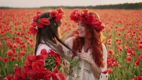 La jeune mère met la guirlande des fleurs de pavot sur la tête de sa fille, mouvement lent banque de vidéos