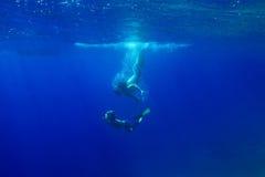 La jeune mère plonge sous l'eau dans l'océan avec son fils L'ONU Image stock