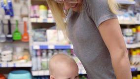 La jeune mère pousse le chariot montant en avant là-dessus L'enfant mignon s'assied dans un chariot d'épicerie Petit bébé et sa m banque de vidéos