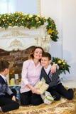 La jeune mère s'asseyant avec des fils et des cadeaux près a décoré la cheminée photos stock