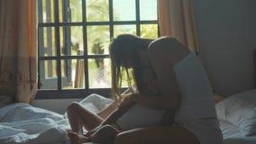 La jeune mère s'assied sur le lit et peigner sa fille dans le mouvement lent banque de vidéos