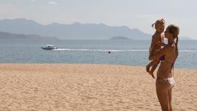 la jeune mère se tient dans la petite fille de bras sur la plage contre la baie clips vidéos