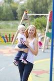 La jeune mère se tient sur des mains de son fils de deux ans Photographie stock