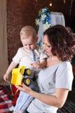 La jeune mère tient le petit camion mignon de fils et de jouet Photo libre de droits