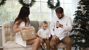 La jeune mère tient un présent dans des ses mains tandis que le jeune père est explosion par feu d'artifice, étincelles et vol de clips vidéos