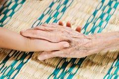 La jeune main touche et tient des mains de dame âgée Images libres de droits