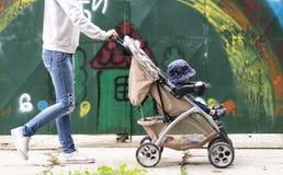 La jeune maman conduit un enfant dans une poussette photos stock