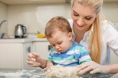 La jeune maman gaie et son petit fils font cuire au four Photo stock