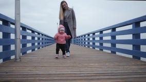 La jeune maman heureuse de femme marche avec une petite fille, embrasse sa fille le long des premières étapes de promenade de mer banque de vidéos