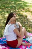 La jeune maman s'inquiète son bébé en rotant la position et l'emplacement sur l'herbe à la couverture colorée, scène extérieure d image stock
