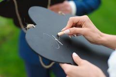 La jeune mariée écrit avec la craie sur un conseil Photo stock