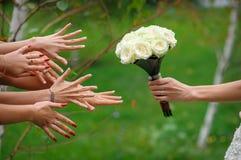 La jeune mariée étire un bouquet Images stock