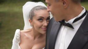 La jeune mariée attirante de brune avec le beau sourire se penche l'épaule de nthe d'o du marié et regarde dans ses yeux Plan rap banque de vidéos
