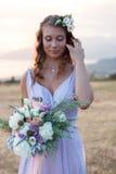 La jeune mariée attirante tient un bouquet de mariage image stock