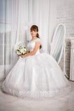La jeune mariée avec le bouquet de mariage s'assied dans un fauteuil Images stock