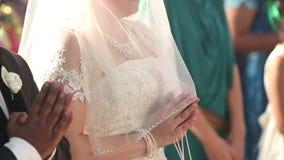 La jeune mariée avec le marié se tenant à l'autel et prient au mariage banque de vidéos