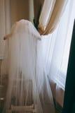 La jeune mariée avec un bouquet posant près du mur Voiles de mariage soufflés dans le vent Photos libres de droits