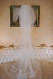 La jeune mariée avec un bouquet posant près du mur Voiles de mariage soufflés dans le vent Photographie stock libre de droits