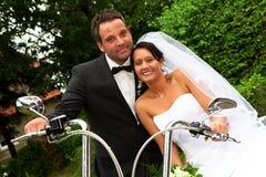 Marié de jeune mariée sur le vélo de Harley Image stock