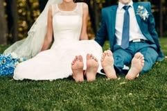 La jeune jeune mariée blonde aux pieds nus et son fiancé s'assied sur l'herbe en parc exotique images stock