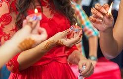 La jeune mariée décorée d'un chandelier décoratif dans ses mains et un signe tient une bougie dans sa main à l'arrière-plan sans Images libres de droits
