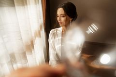 La jeune mariée dans la belle robe se reposant sur la chaise à l'intérieur dans l'intérieur blanc de studio aiment à la maison Ti photographie stock libre de droits